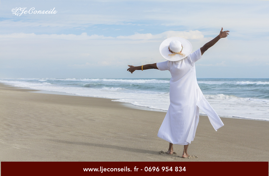 Happy senior African American woman dancing alone on a deserted tropical beach