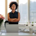 Portrait of confident young businesswoman standing at her desk with arms crossed and looking at camera. African woman with curly hair standing at her workplace.
